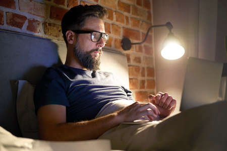Side view of man with glasses working late in bed Standard-Bild