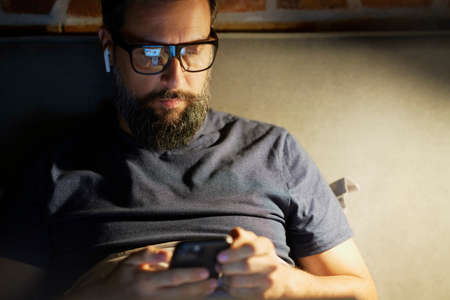 Man with mobile phone lying in bed Standard-Bild