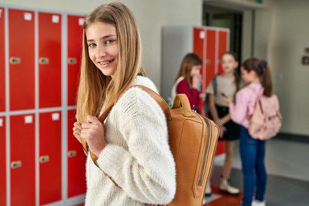 Portrait of smiling schoolgirl standing in school corridor
