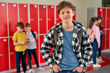 Portrait of teenager standing in corridor near lockers