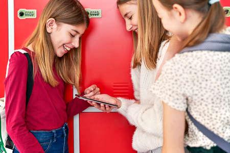 Group of smiling schoolgirls using smartphone in corridor near lockers