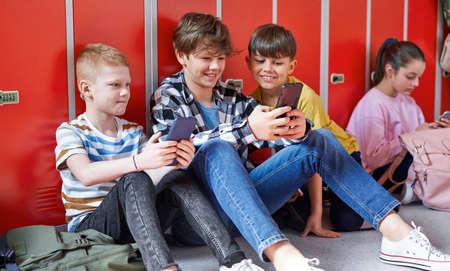 School children sitting and using smartphone at school Standard-Bild