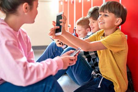 School children sitting on the floor and using smartphone Standard-Bild