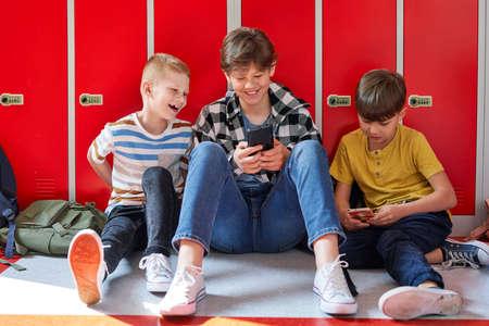 Smiling friends sitting and using smart phone in school corridor Standard-Bild