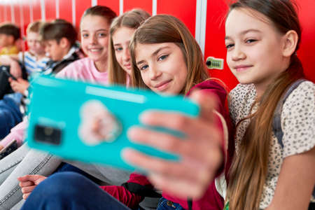 Schoolgirls make smiling photos on the corridor