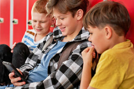 Three schoolboys sitting and looking the phone