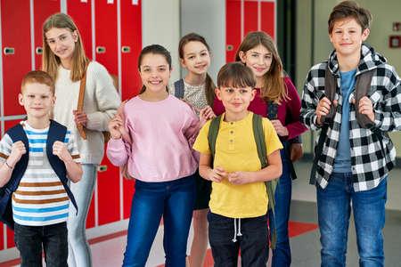 Group of smiling school children standing in corridor Standard-Bild