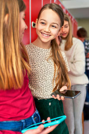 Schoolchildren smile at each other holding the mobile phone