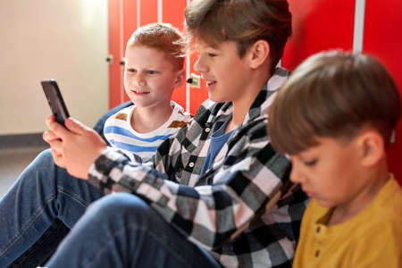 Three schoolboys sitting on the corridor and using phone
