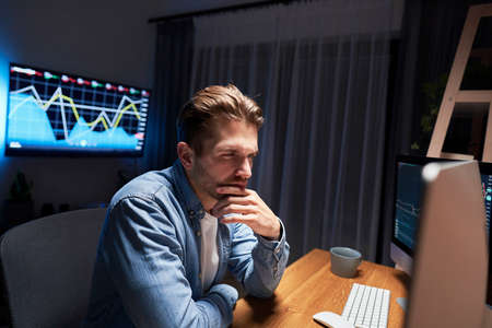 Young man working late at home office