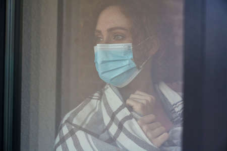 Caucasian red head woman with protective mask standing indoors next to the window 스톡 콘텐츠