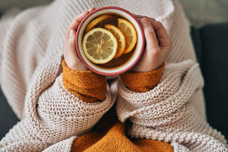 Top view of woman holding cup of hot tea
