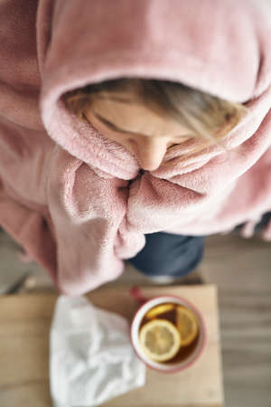 Top view of woman covered with warm blanket