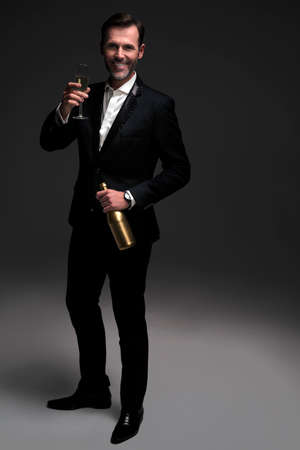 Elegance man celebrating with bottle of champagne