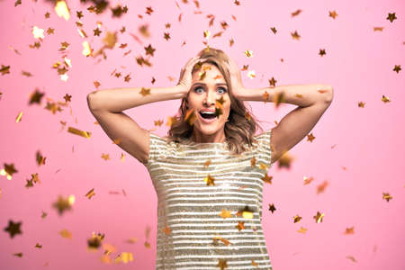 Blonde woman have fun with gold confetti