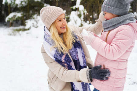 Mom with little girl spending winter day outdoors 스톡 콘텐츠