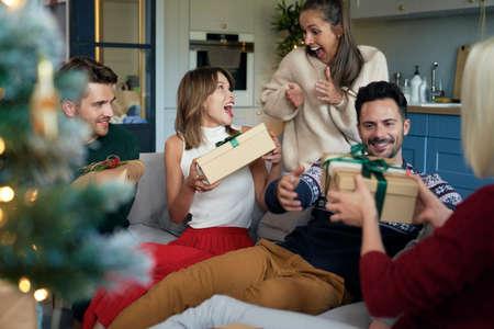 Joyful friends unwrapping Christmas presents