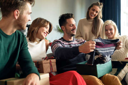Man receiving ugly sweater as Christmas gift 스톡 콘텐츠
