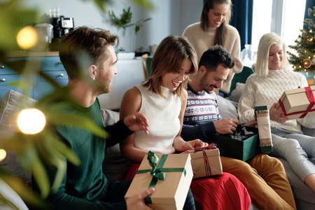 Group of friends opening Christmas presents 스톡 콘텐츠