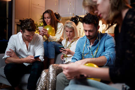 Friends focused on mobile phones on party