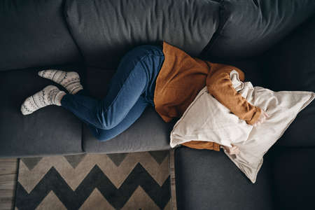 Woman with emotional problems lying on the couch