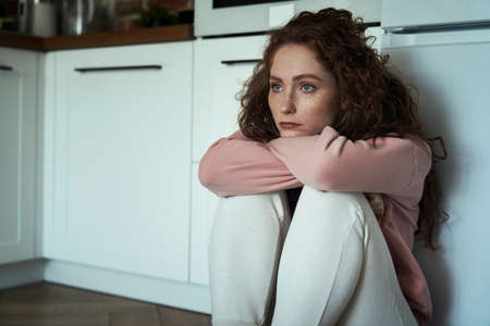 Thoughtful young caucasian woman sitting on floor in the kitchen and sadly looking away