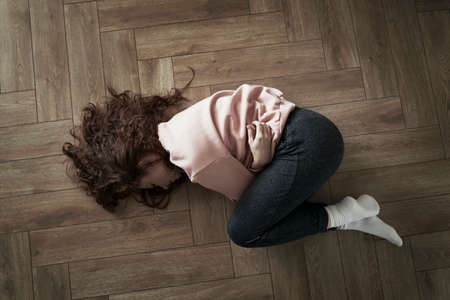 Top view of young caucasian woman lying on floor and having strong stomachache 스톡 콘텐츠