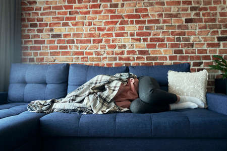 Woman with emotional problems lying on the couch and covered with a blanket 스톡 콘텐츠