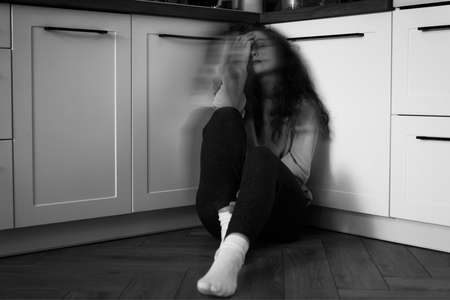 Black and white image of thoughtful young caucasian woman sitting on floor in the kitchen 스톡 콘텐츠
