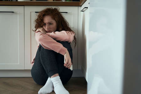 Thoughtful young caucasian woman sitting on floor in the kitchen