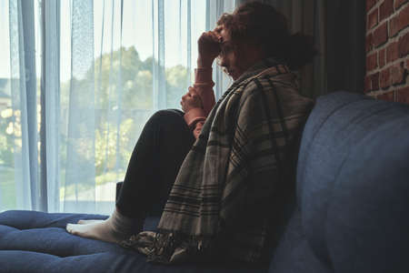 Depressed young caucasian woman covered with blanket on sofa