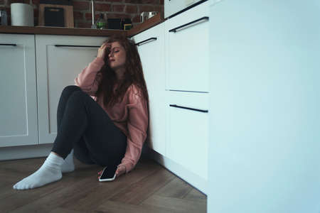 Anxious young caucasian woman sitting on floor holding mobile phone