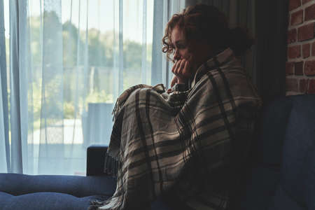Depressed young caucasian woman sitting on sofa in silence covered with blanket