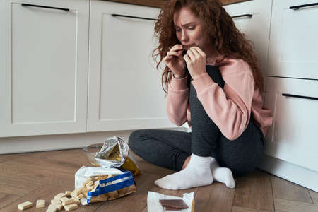 Young caucasian woman with eating disorder eating greedily on the floor