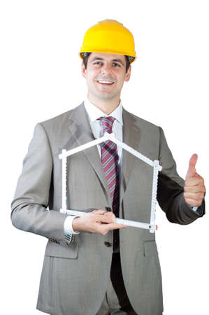 Construction contractor businessman holding a wooden yard stick shaped like a symbolic house, and showing thumb up. Isolated on white background. photo