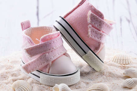 Pink children's shoes on white sand, seashells lie next to small sneakers.