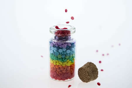 Colorful multicolor beads or tablets are poured into a glass bottle. A rainbow in a bottle. Magic pills.