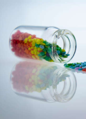 Colorful multicolor beads or tablets are poured into a glass bottle. A rainbow in a bottle. Magic pills. Reflection Фото со стока