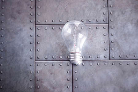 An electric glass bulb lies on a gray iron background. Free space for text.