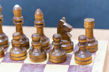 Playing wooden chess on a chessboard. Tactics and strategy. Black and white shapes.