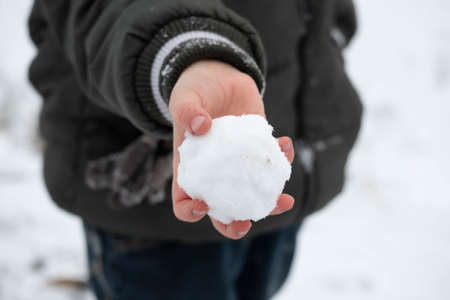 A child's hand holding a round snowball.