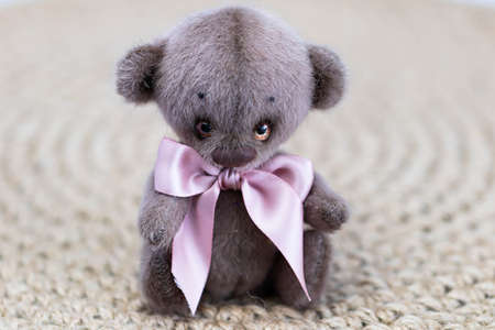 A cute toy teddy bear with a pink bow sits on a wicker background