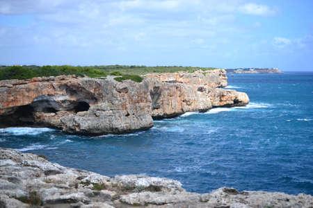 Rock formations for climbing at Cala Sa Nau beach and Cala dOr city, Palma Mallorca Island, Spain Banco de Imagens - 115624503