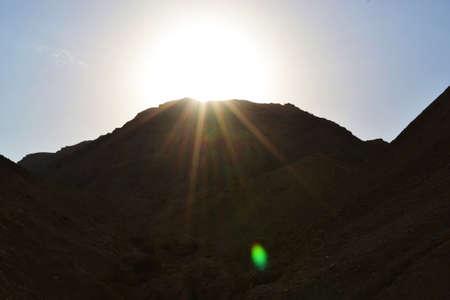 Sun behind mountain, Qumran caves in Qumran National Park, Judean desert hike, Israel Stock Photo
