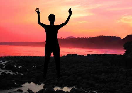 A woman silhouette with his arms raised in worship Stock Photo