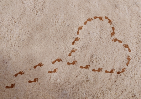 Heart shape with footprints on the sand  Stock Photo
