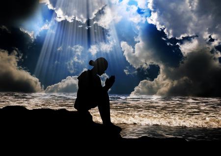 perdonar: Silueta de ni�a rezando pac�ficamente Foto de archivo