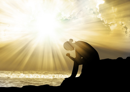 Woman praying to god at sunset Stock Photo
