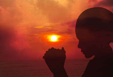 worship praise: Silhouettes of a women praying at sunset