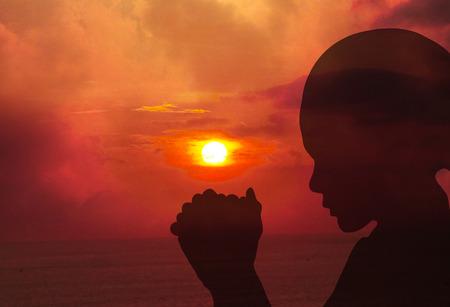 mujeres orando: Siluetas de una mujer rezando en la puesta del sol